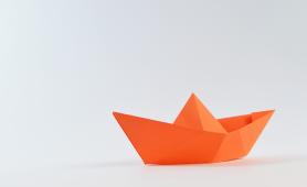 papierowa łódka symbolizująca pracę nad strategią